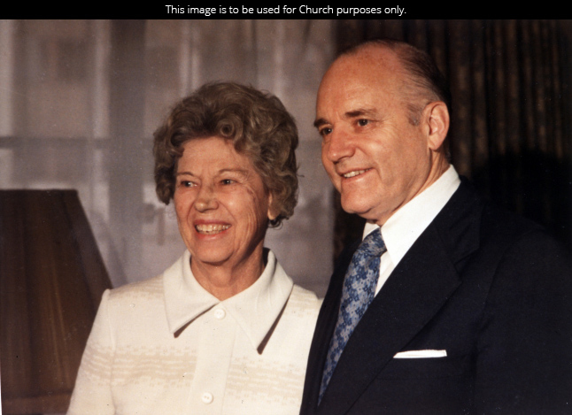 President Howard W. Hunter in a white shirt, blue tie, and black suit next to his wife Clara Jeffs Hunter in a white jacket.