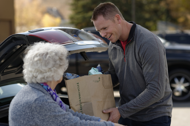 A man helping an elderly woman load groceries into her car in a parking lot.