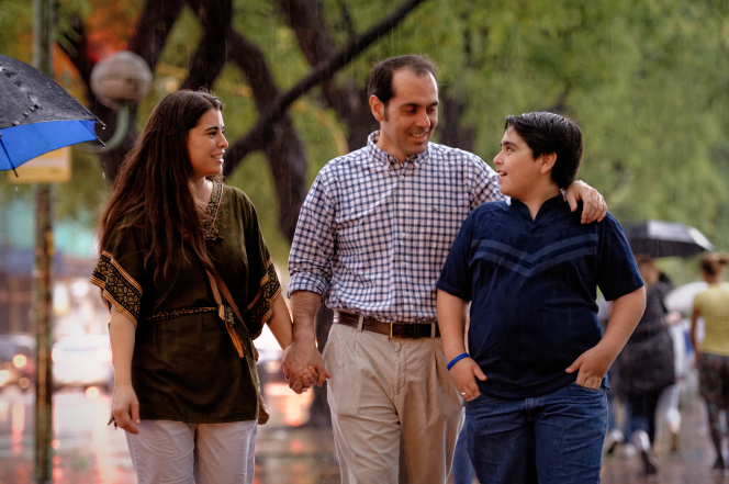 A father and mother holding hands while walking with their teenage son in Argentina.