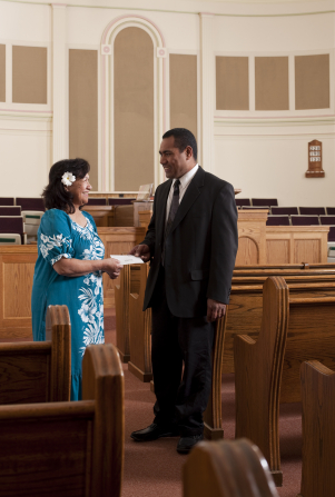 A woman in a blue dress standing in a chapel, giving a tithing envelope to her bishop.