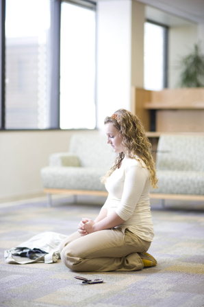 A young woman with curly blond hair kneeling in a room and praying.