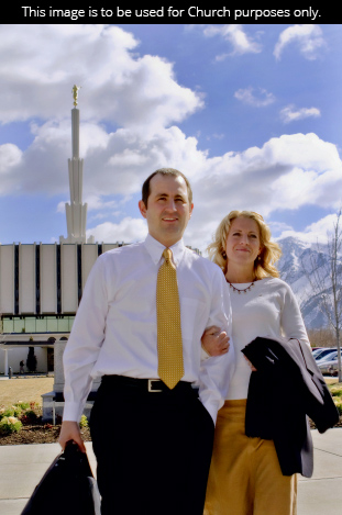 A couple walking with linked arms outside the Provo Utah Temple on a sunny day.