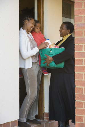A woman standing at a door and giving groceries to another woman, who is holding a child.
