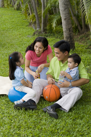 A father, mother, son, and daughter sitting outside on the grass with a basketball.