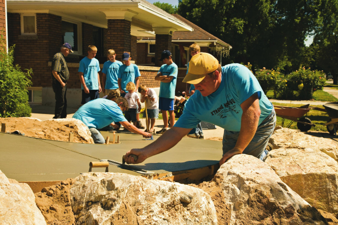Youth and adults wearing blue T-shirts and doing a service project on a sidewalk.