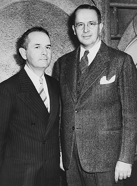 Ezra Taft Benson standing beside Spencer W. Kimball, who is wearing a black striped suit, in October 1943.