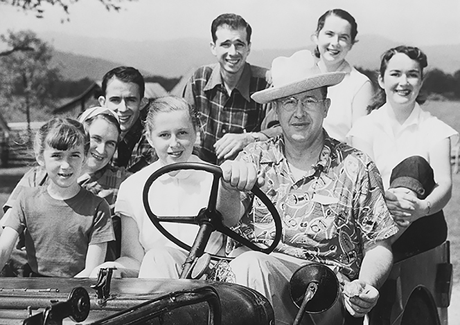 President Benson wearing a hat, sitting at the steering wheel of a car with his children next to him and behind him.