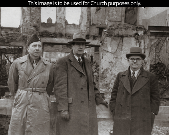 Elder Benson around 1946, standing with two missionary companions in long coats and hats in Europe.