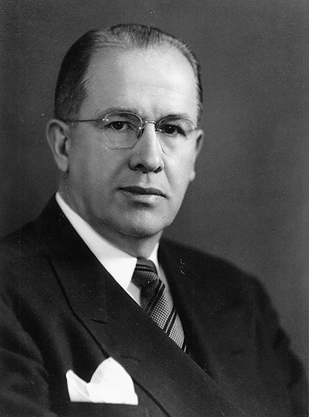 President Ezra Taft Benson in a white shirt, striped tie, and black suit with a handkerchief in his front pocket, around 1949.