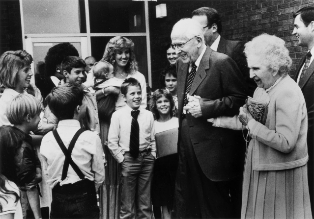 President Ezra Taft Benson walking and holding hands with his wife, Flora A. Benson, while greeting children.