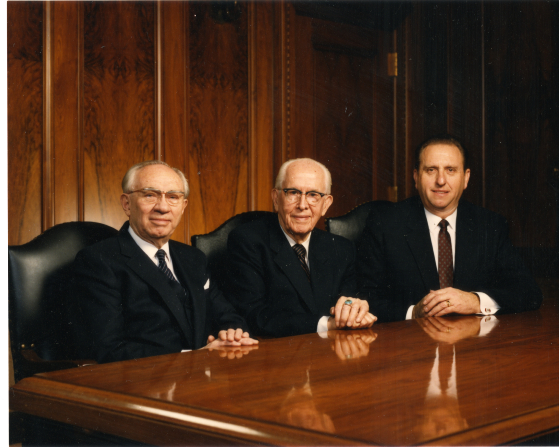 President Ezra Taft Benson sitting at a table between his two counselors in the First Presidency, President Gordon B. Hinckley and President Thomas S. Monson.