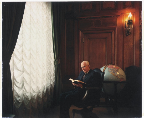 President Benson sitting near a tall window, reading scriptures, with a globe behind him.