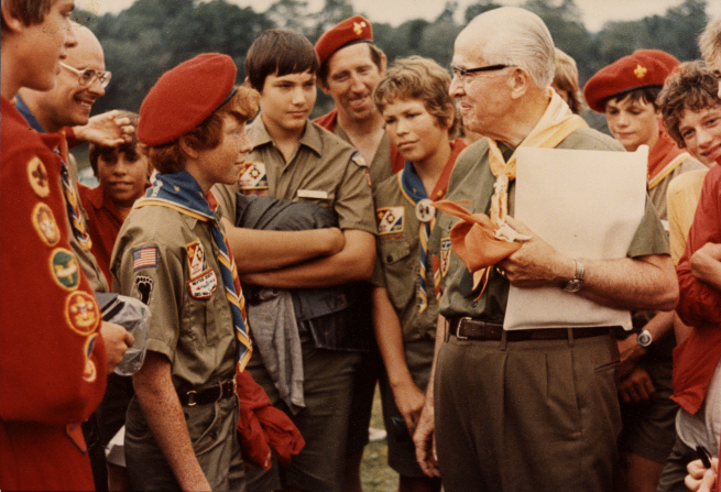 President Ezra Taft Benson in Scout uniform, holding a folder and standing with Boy Scouts, around 1977.