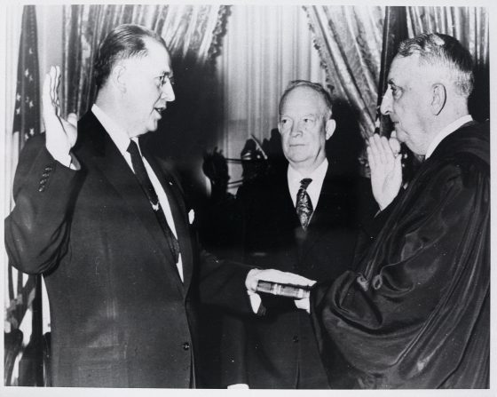 Ezra Taft Benson raising his right arm while being sworn in as United States secretary of agriculture by Chief Justice Vinson, with President Eisenhower looking on.