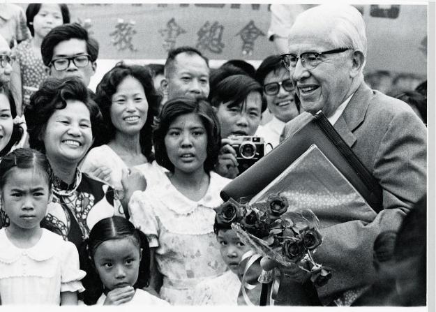 President Benson holding a package and a bouquet of roses, surrounded by Church members in Taiwan, around 1980.