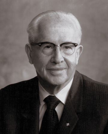 President Ezra Taft Benson around 1962, smiling and wearing a white shirt, a tie, a suit, and glasses.