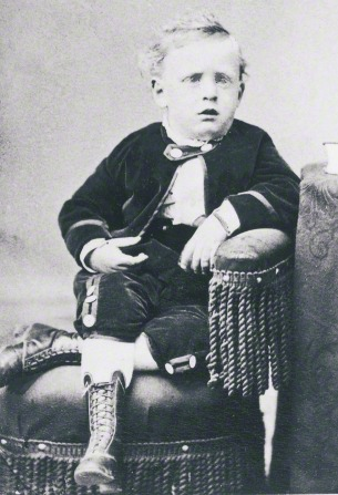 George Albert Smith around four years old, wearing a jacket, pants, and lace-up boots, sitting in a chair and leaning his arm on the armrest.