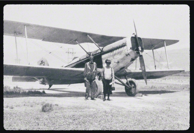 George Albert Smith in aviator clothes, standing by his wife, Lucy Smith, in front of an airplane.