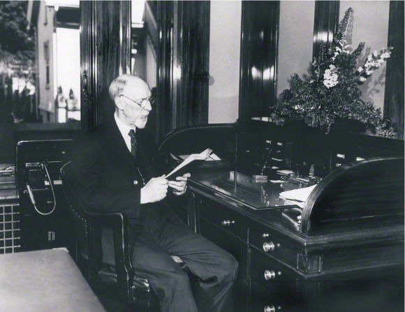 President George Albert Smith sitting at a desk in his office, reading a book.