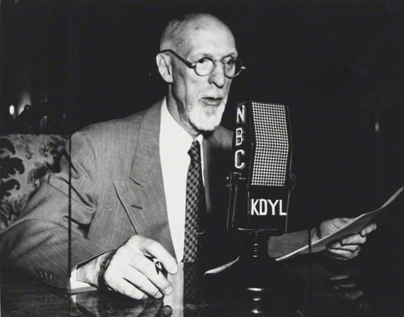 President George Albert Smith sitting at a desk and speaking into a microphone labeled NBC and KDYL, the local Salt Lake radio station.