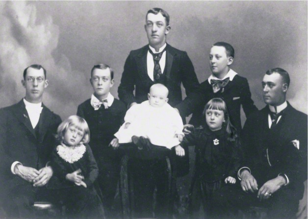 George Albert Smith with his brothers in suits and ties and his sisters in dresses.