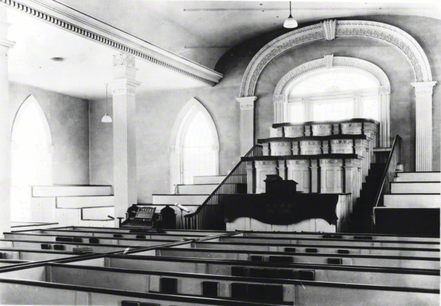A view inside the Kirtland Temple between 1880 and the 1970s, showing benches, a podium, and large windows.