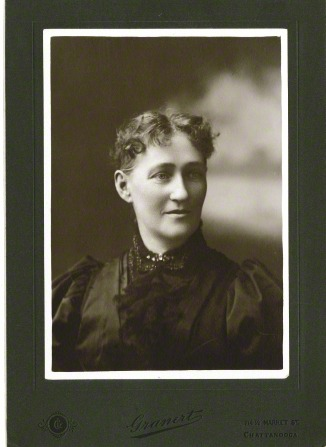 A portrait of George Albert Smith's mother, with short, curly dark hair and a blouse with lace.
