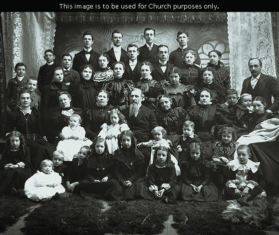 A large group portrait of Joseph Fielding Smith with his five wives and children, taken on his 60th birthday in November 1898.