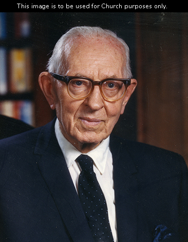 President Joseph Fielding Smith sitting in his office, wearing a white shirt, a dark suit, a dotted tie, and glasses.