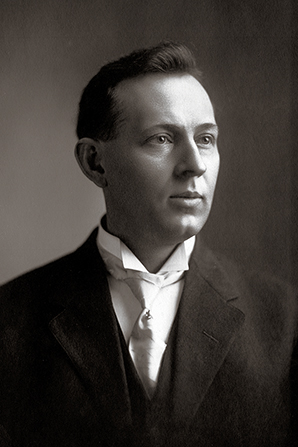 Elder Joseph Fielding Smith in a black suit, white shirt, and white tie, shortly after being ordained an Apostle in 1910.
