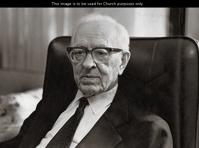 President Joseph Fielding Smith wearing a white shirt, a tie, a suit, and glasses, sitting in a black chair.