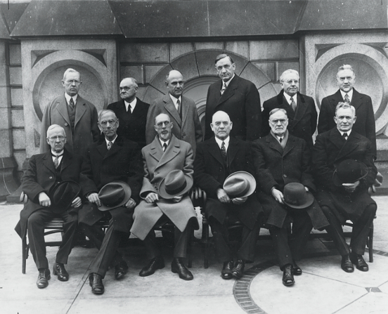 The Quorum of the Twelve Apostles in 1921, standing and seated in two rows: Joseph Fielding Smith, James E. Talmage, Stephen L Richards, Richard R. Lyman, Melvin J. Ballard, John A. Widtsoe, Rudger Clawson, Reed Smoot, George Albert Smith, George F. Richards, Orson F. Whitney, and David O. McKay.