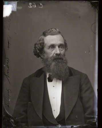 Elder Lorenzo Snow in a vest, suit, and bow tie, with curly hair and a long beard.