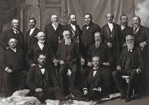 The Quorum of the Twelve Apostles in 1898, standing and sitting in three rows: Anthon H. Lund, John W. Taylor, John Henry Smith, Heber J. Grant, Brigham Young Jr., George Teasdale, Rudger Clawson, Marriner W. Merrill, Francis M. Lyman, George Q. Cannon, Lorenzo Snow, Joseph F. Smith, Franklin D. Richards, Matthias F. Cowley, and Abraham O. Woodruff.