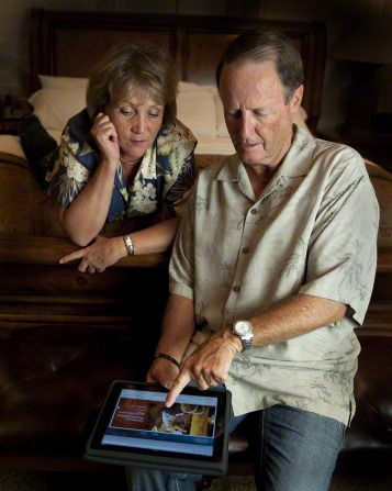 A husband sitting at the end of a bed and his wife resting her head on her arm while they look at LDS.org on a tablet.