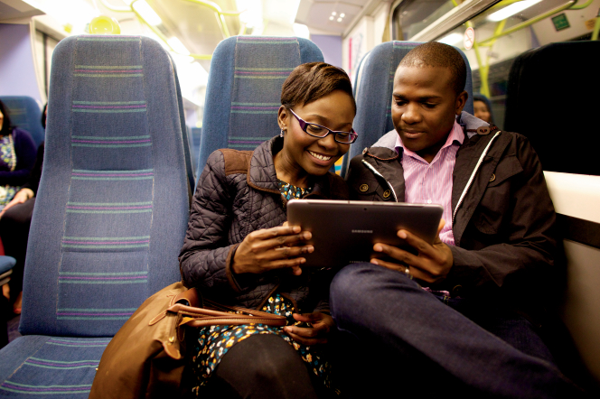 A couple sitting in tall blue seats on a train, looking at a tablet together.