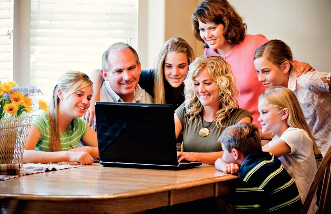A young woman sits at a dining room table and works on a laptop while her mother and father and five siblings sit around and watch what she is doing.