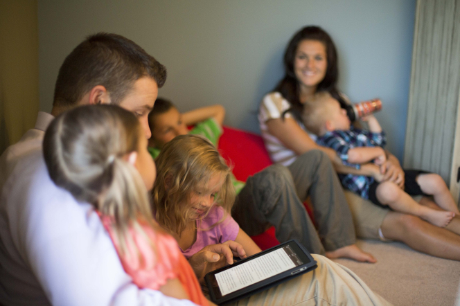 A father sits down with his arm around one of his daughters and reads from a tablet while another daughter looks at the tablet with him.