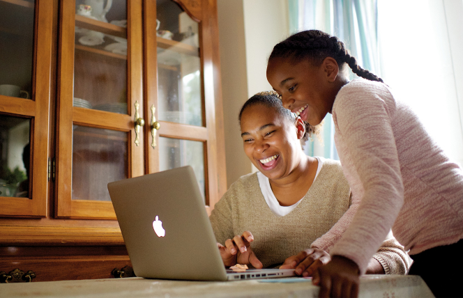 A mother sits at a dining room table and works on a laptop while her daughter stands next to her and looks at the laptop screen.