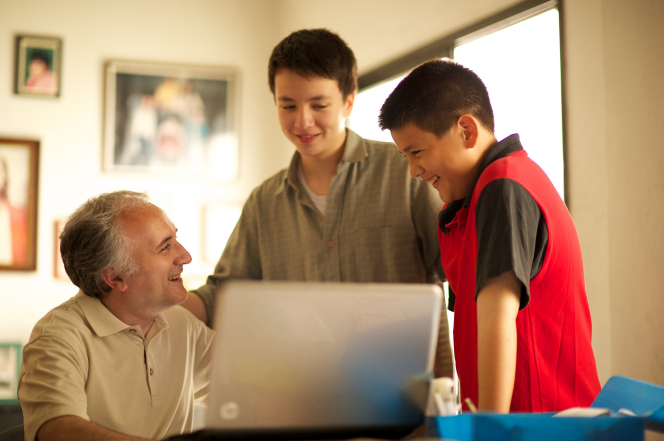 A father sits in front of his laptop at a table while his two sons stand next to him, one looking at the monitor and the other looking at the father.