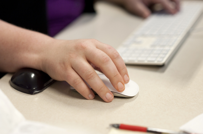 A woman's hand is pictured using a computer mouse, with her other hand resting on a keyboard.