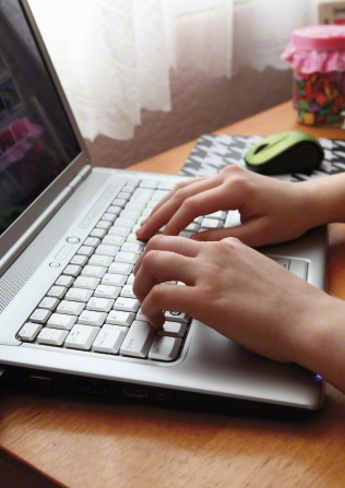 Hands are seen typing on a silver laptop with a computer mouse next to it.
