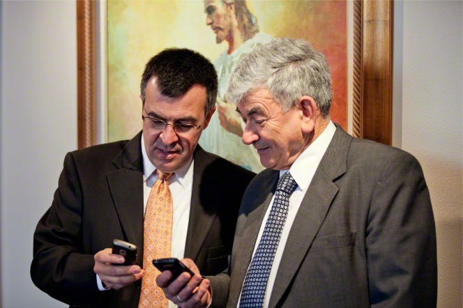 Two older men stand in a meetinghouse next to a picture of Christ and look at the smartphones in their hands.