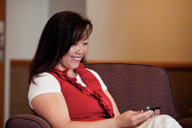 A woman with dark brown hair sits in an armchair at a meetinghouse and smiles at her smartphone.
