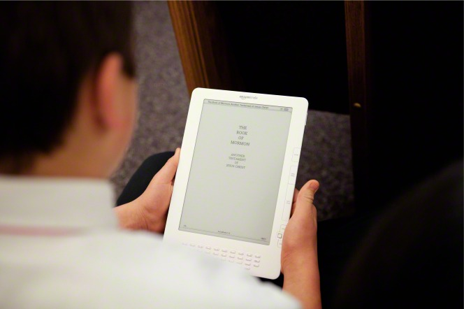 A young boy sitting in a meetinghouse, reading the Book of Mormon from a white tablet.