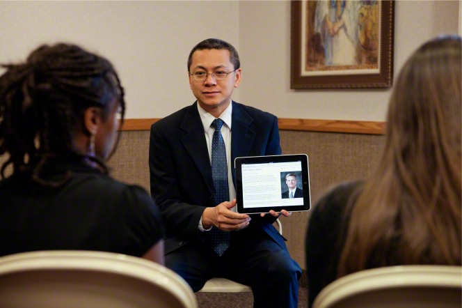A teacher sitting in front of his class and holding up a black iPad to show his students a talk by Elder Bednar.