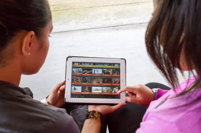 Two young women with dark brown hair hold a tablet and look at a menu on the screen.