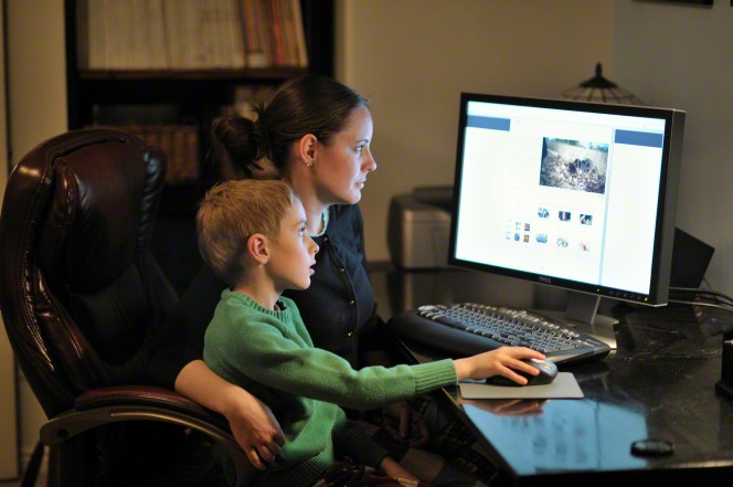 A mother sits in a brown office chair at her computer with her son on her lap and looks at LDS.org.