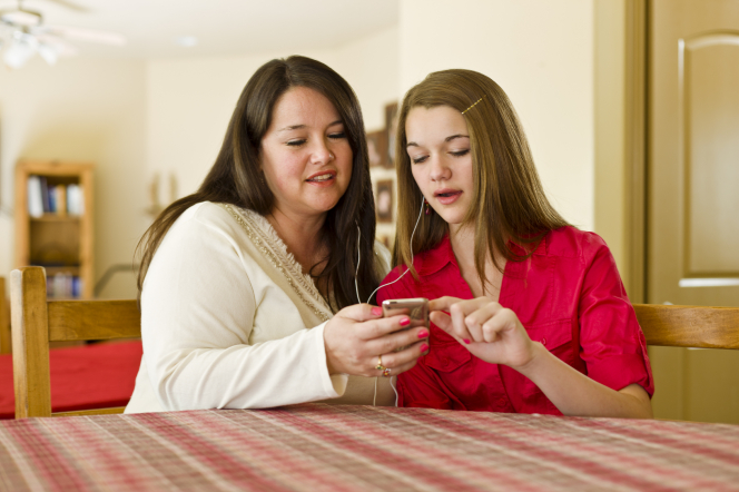 A mother and daughter sitting at a table and sharing headphones to listen to an MP3 player together.