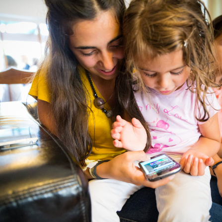 A little girl with light brown hair sits on her mother's lap and looks at a smartphone with her.